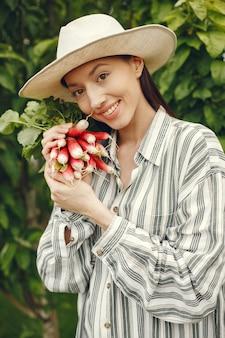Kobieta w kapeluszu trzyma świeże rzodkiewki