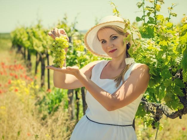 Kobieta w kapeluszu, trzymając się za ręce, pędzel zielonych winogron.