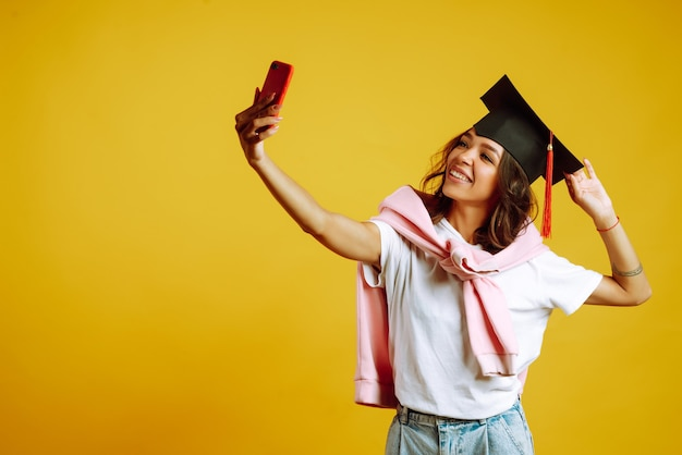 Kobieta w kapeluszu ukończenia szkoły na głowie bierze selfie na żółto