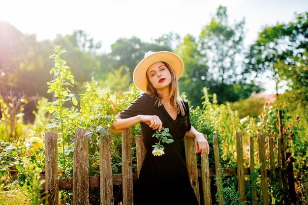 Kobieta w kapeluszu w lato wsi ogródzie