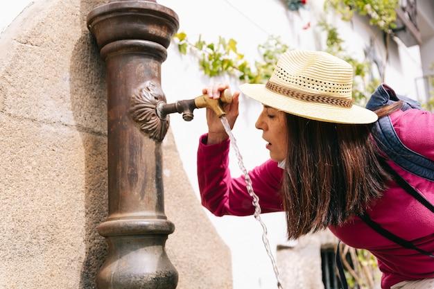 Kobieta w kapeluszu wodą pitną z fontanny