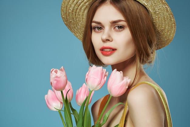 Kobieta w kapeluszu z bukietem kwiatów makijaż urok dekoracja lato niebieskie tło