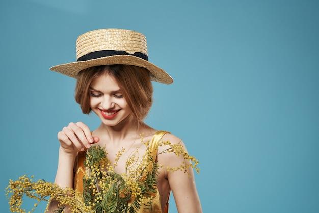 Kobieta w kapeluszu z bukietem kwiatów wakacje dzień kobiet urok niebieskie tło. wysokiej jakości zdjęcie