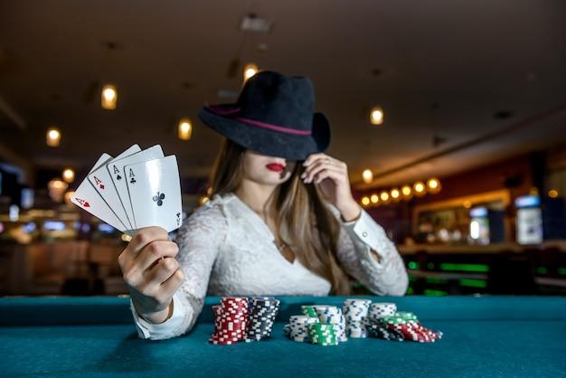 Kobieta w kapeluszu z kartami do gry i żetonami w kasynie