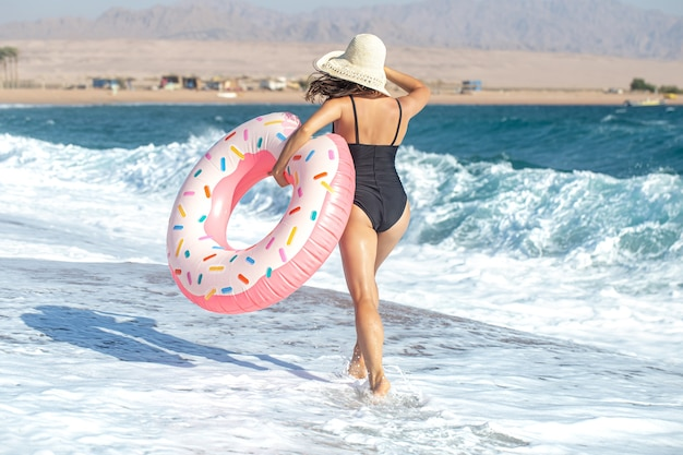 Kobieta w kapeluszu z kółeczkiem w kształcie pączka nad morzem. pojęcie wypoczynku i rozrywki na wakacjach.