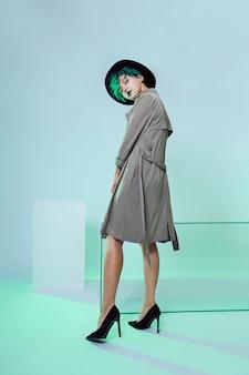 Kobieta w kapeluszu z kreatywnym zielonym farbowaniem włosów i makijażu, toksyczne kosmyki włosów. jasny kolor kręcone włosy na głowie dziewczyny, profesjonalny makijaż. kobieta z tatuażem w płaszczu