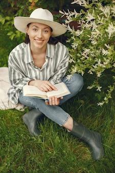 Kobieta w kapeluszu z książką w ogrodzie