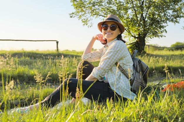 Kobieta w kapeluszu z plecaka obsiadaniem na trawie cieszy się lato naturę