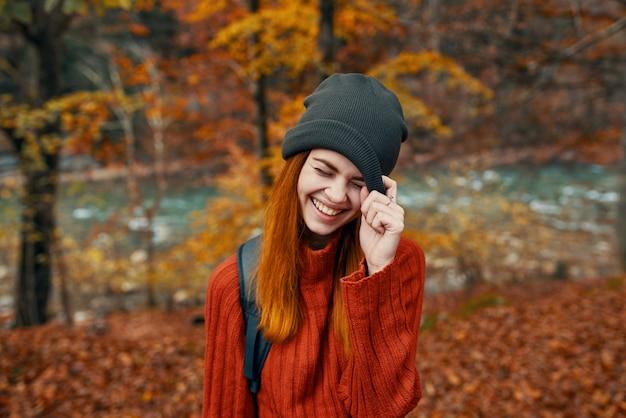 Kobieta w kapeluszu z plecakiem i swetrem odpoczywa w jesiennym lesie nad rzeką
