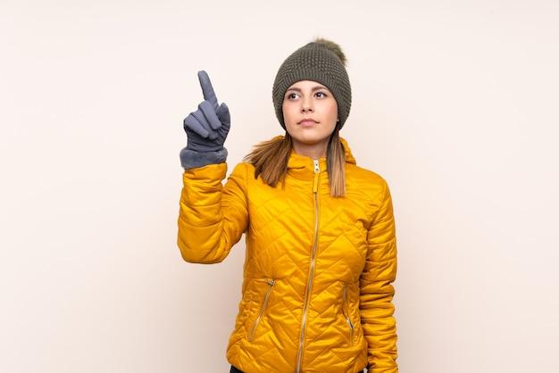 Kobieta w kapeluszu zimowym na białym tle ściany dotykając przezroczystego ekranu