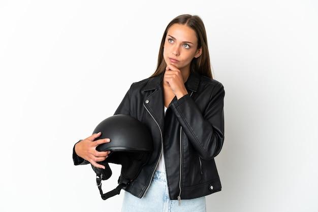 Kobieta w kasku motocyklowym na białym tle ma wątpliwości