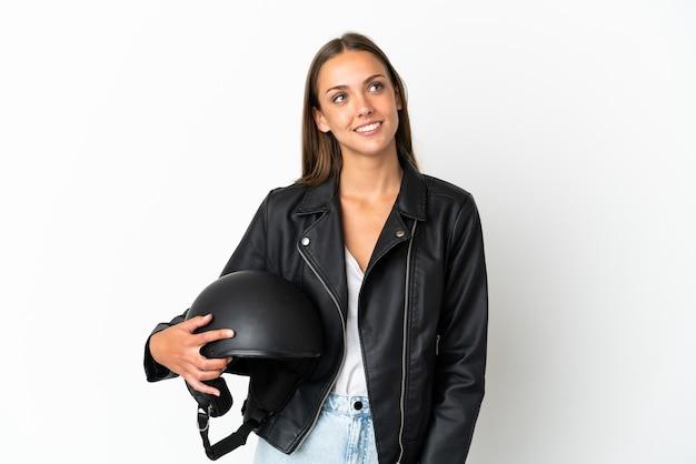 Kobieta w kasku motocyklowym na białym tle myśli pomysł, patrząc w górę