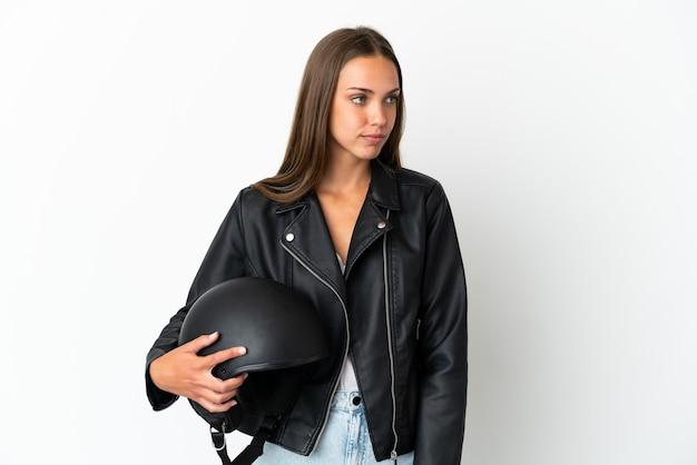 Kobieta w kasku motocyklowym na białym tle patrząc z boku