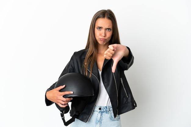 Kobieta w kasku motocyklowym na białym tle pokazując kciuk w dół z negatywnym wyrazem twarzy