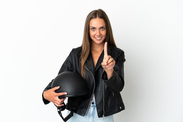 Kobieta w kasku motocyklowym na białym tle pokazująca i unosząca palec