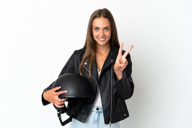 Kobieta w kasku motocyklowym na białym tle uśmiechnięta i pokazująca znak zwycięstwa