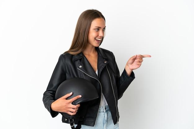 Kobieta w kasku motocyklowym na białym tle wskazując palcem w bok i przedstawia produkt
