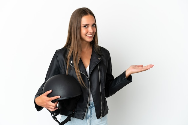 Kobieta w kasku motocyklowym na białym tle wyciągając ręce na bok na zaproszenie do przyjazdu