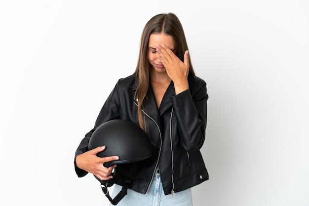 Kobieta w kasku motocyklowym na białym tle ze zmęczoną i chorą miną