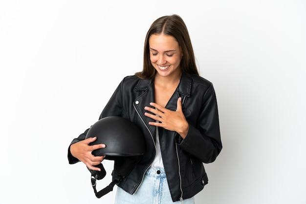 Kobieta w kasku motocyklowym na odosobnionym białym tle często się uśmiecha