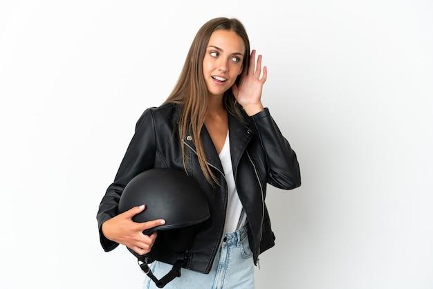 Kobieta w kasku motocyklowym na odosobnionym białym tle słucha czegoś, kładąc rękę na uchu