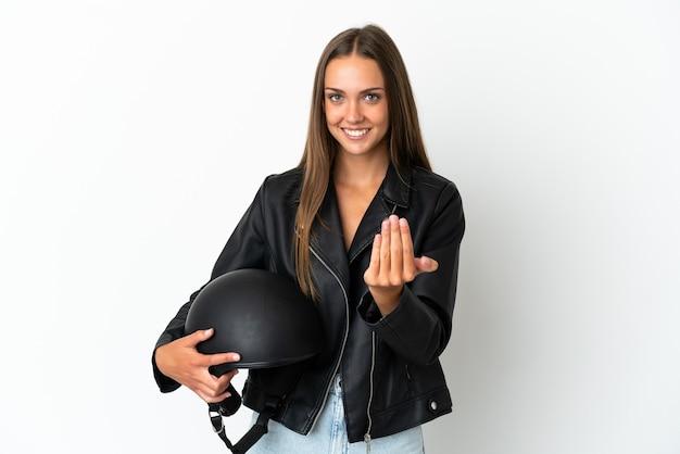 Kobieta w kasku motocyklowym na pojedyncze białe tło zaprasza do przyjścia z ręką. cieszę się, że przyszedłeś