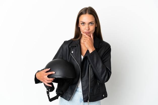 Kobieta w kasku motocyklowym nad odosobnionym białym tłem myślenia