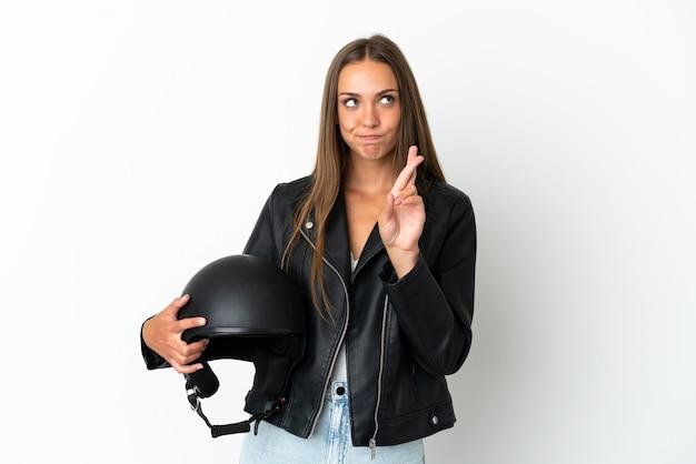 Kobieta w kasku motocyklowym odizolowana ze skrzyżowanymi palcami i życząca wszystkiego najlepszego