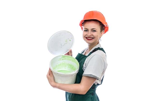 Kobieta w kasku z wiadrem z farbą na białym tle