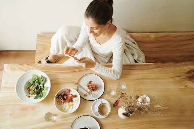 Kobieta w kawiarni je śniadanie i przy użyciu telefonu