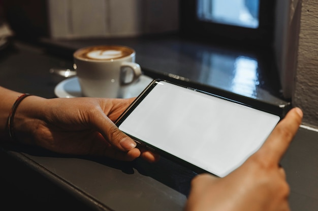 Kobieta w kawiarni korzystająca z telefonu komórkowego