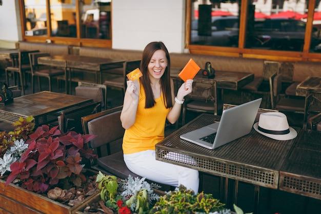 Kobieta w kawiarni na świeżym powietrzu siedzi przy stole z nowoczesnym komputerem typu laptop, trzyma w ręku kartę kredytową banku i paszport