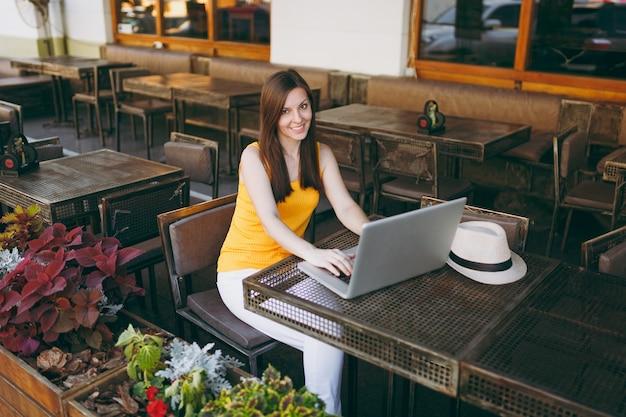 Kobieta w kawiarni na świeżym powietrzu w kawiarni siedząc przy stole, pracując na nowoczesnym laptopie, relaksując się w restauracji w czasie wolnym