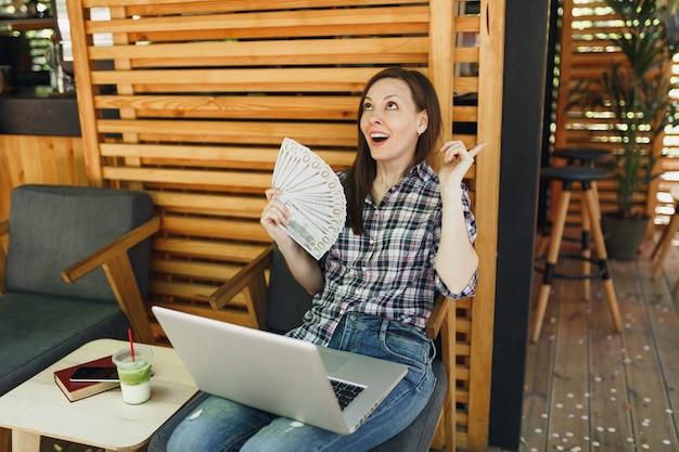 Kobieta w kawiarni na świeżym powietrzu w kawiarni siedząc z nowoczesnym komputerem przenośnym, trzymaj w ręku kilka banknotów dolarów, gotówkę