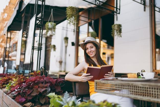 Kobieta w kawiarni na zewnątrz ulicy kawiarnia siedzi przy stole w kapeluszu, czyta książkę z filiżanką cappuccino, ciasto, relaks w restauracji w czasie wolnym