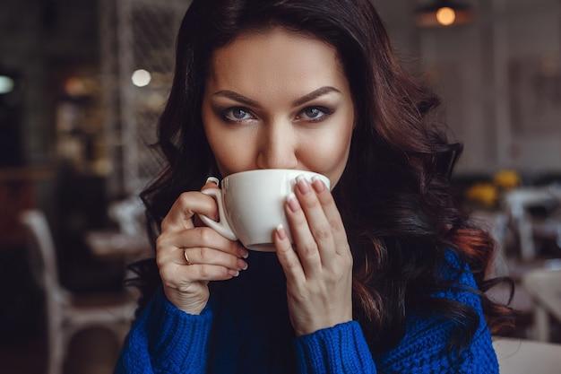 Kobieta w kawiarni siedzi przy stole, pije kawę i patrzy w okno. kobieta w czerwonej szmince iw niebieskim swetrze czeka na spotkanie, dużo rozmawia przez telefon i dużo się uśmiecha.