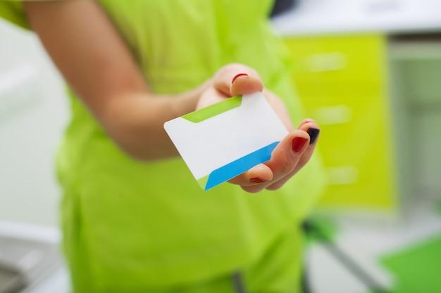 Kobieta w klinice dentystycznej gospodarstwa puste wizytówki