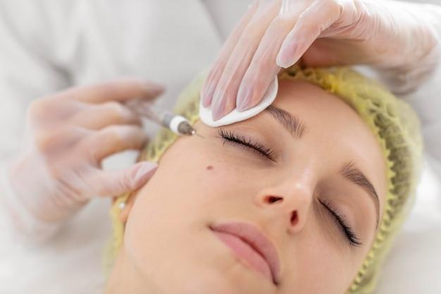 Kobieta w klinice kosmetycznej do leczenia wypełniaczem