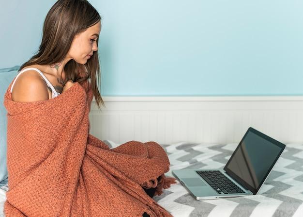 Kobieta w koc w domu pracuje na laptopie podczas pandemii