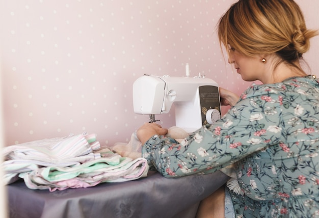 Kobieta w kolorowej sukience szyje w domu na maszynie do szycia