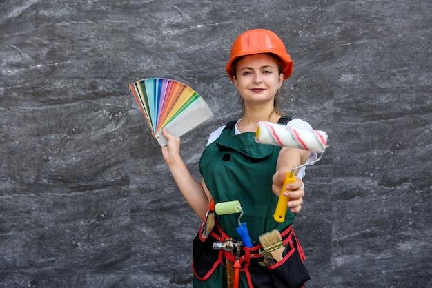 Kobieta w kombinezonie gospodarstwa rolkę i próbkę koloru na abstrakcyjnym tle