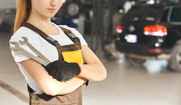 Kobieta w kombinezonie i ochronne rękawiczki pozuje w warsztacie