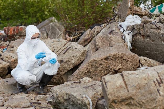 Kobieta w kombinezonie ochronnym siedząca na skale i pobierająca próbki ziemi do analizy