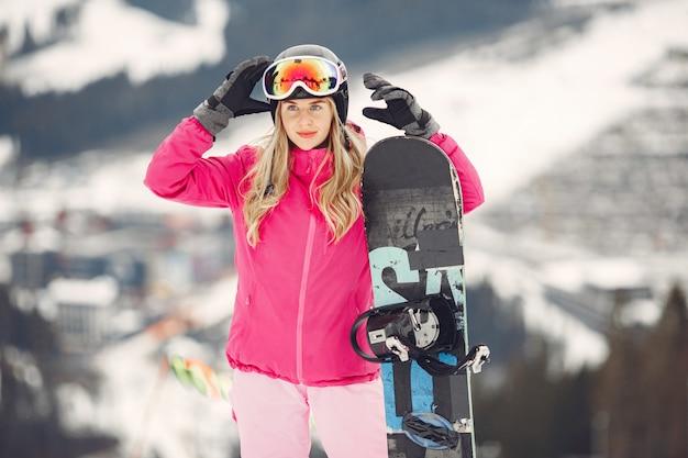 Kobieta w kombinezonie snowboardowym. sportsmenka na górze ze snowboardem w rękach na horyzoncie. koncepcja sportu
