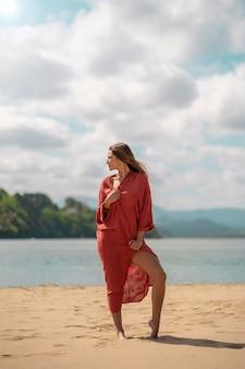 Kobieta w koralowej długiej letniej sukience odwracająca wzrok na plażę