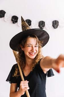 Kobieta w kostium czarownicy z czarną miotłą