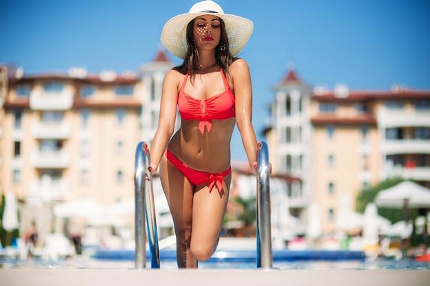 Kobieta w kostiumie kąpielowym przy basenie