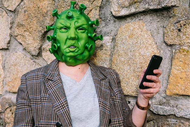 Kobieta w kostiumie - maska koronawirusa covid-19, patrząc na telefon komórkowy