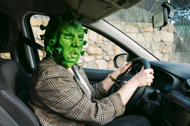 Kobieta w kostiumie - maska koronawirusa covid-19 prowadząca samochód
