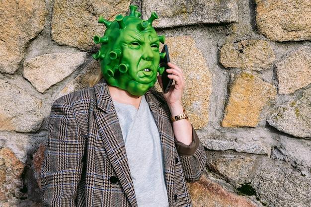 Kobieta w kostiumie - maska koronawirusa covid-19 rozmawiająca przez telefon komórkowy